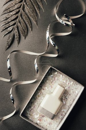 perfume bottle in box, silver ribbons and shiny decorative leaves on grey