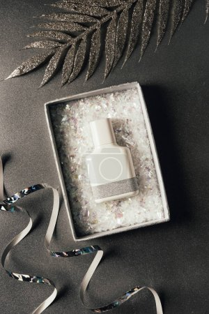 top view of perfume bottle in box, silver ribbons and shiny decorative leaves on grey