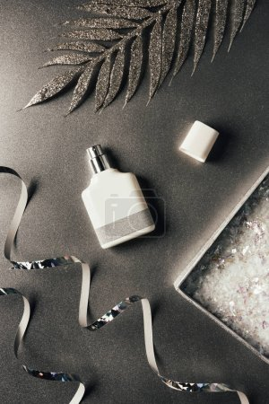 top view of perfume bottle, silver ribbons and shiny decorative leaves on grey