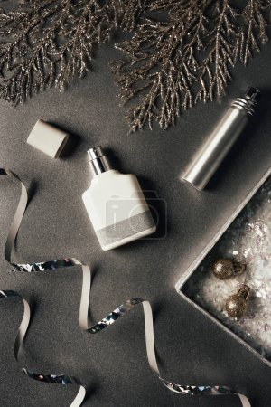 top view of perfumes, shiny ribbons and christmas baubles on grey