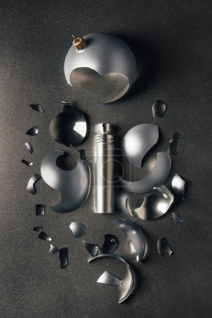 top view of perfume and broken silver christmas bauble on grey