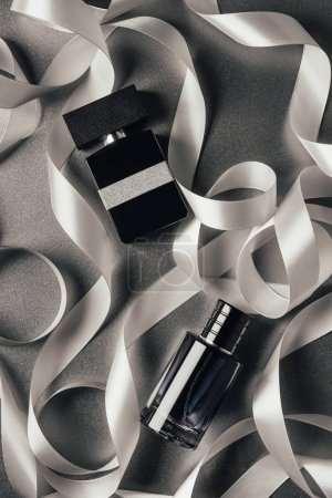 top view of bottles of perfumes and white ribbons on grey