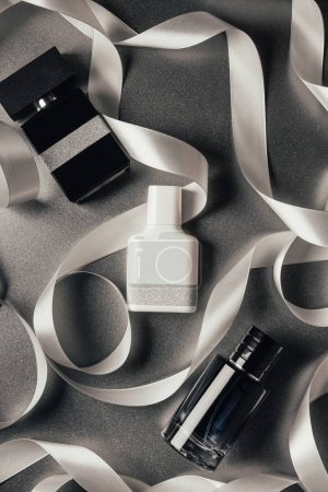 Photo for Top view of bottled perfumes and white ribbons on grey - Royalty Free Image