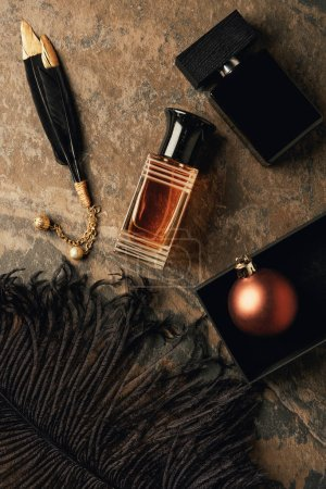top view of perfumes, decorative black feathers and shiny christmas ball