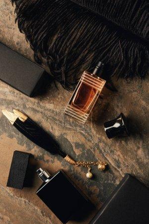 Foto de Botellas de perfume, cajas y decorativos plumas negras sobre la superficie erosionada marrón - Imagen libre de derechos