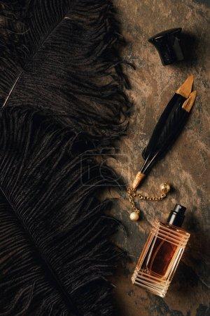 Foto de Botella de perfume y decorativos plumas negras sobre la superficie erosionada marrón - Imagen libre de derechos