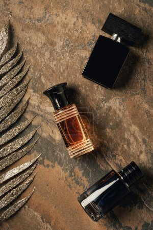 top view of bottled perfumes and decorative golden leaves on brown weathered surface