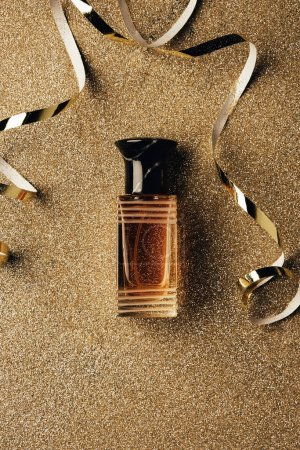 top view of perfume bottle and golden ribbons in shiny surface