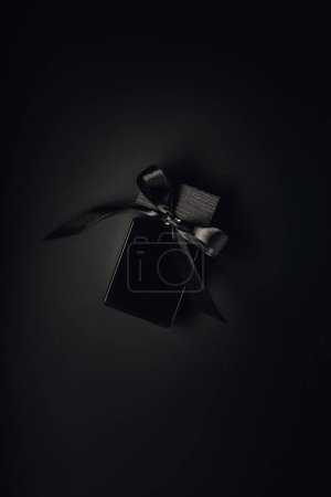 top view of black perfume bottle with ribbon on black background