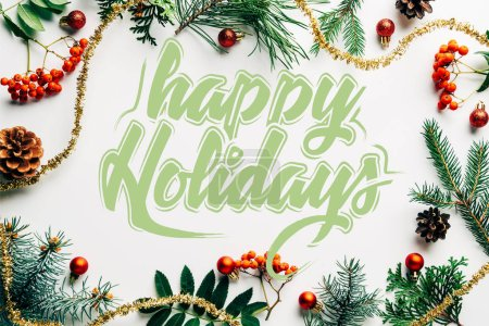 "flat lay with festive arrangement of pine tree branches, common sea buckthorn and christmas decorations on white tabletop with ""happy holidays"" lettering"