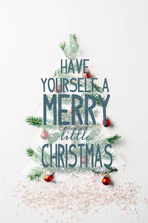 """Photo for Top view of green pine branch decorated as festive christmas tree with glitters on white background with """"have yourself a merry little christmas"""" inspiration - Royalty Free Image"""