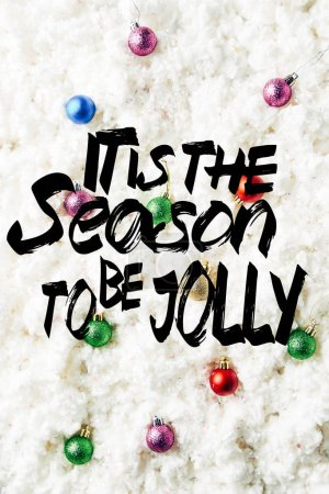 """top view of colorful christmas toys on white cotton wool background with """"it is the season to be jolly"""" inspiration"""
