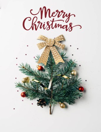 "Photo for Top view of green pine branch decorated as festive christmas tree with bow on white background with ""merry christmas"" lettering - Royalty Free Image"