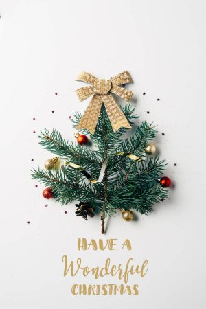 """top view of green pine branch decorated as festive christmas tree with bow on white background with """"have a wonderful christmas"""" inspiration"""