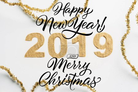 "top view of 2019 year sign made of golden glitters and garlands on white backdrop with ""happy new year 2019 and merry christmas"" lettering"