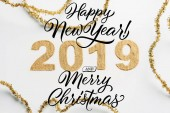 top view of 2019 year sign made of golden glitters and garlands on white backdrop with