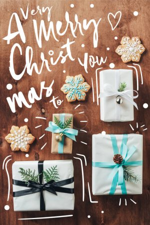 "top view of gift boxes and christmas cookies with icing on wooden background with ""a very merry christmas to you"" inspiration"