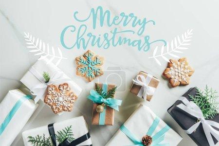 """Foto de Lay Flat con cajas de regalo de Navidad y las galletas de copo de nieve sobre fondo de mármol con inscripción """"Feliz Navidad"""" - Imagen libre de derechos"""