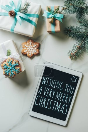 """Photo for Top view of christmas presents, snowflake cookies and digital tablet with """"wishing you a very merry christmas"""" inspiration on screen on marble background - Royalty Free Image"""