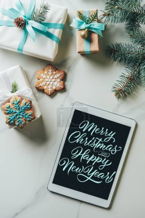 """Photo for Top view of christmas presents, snowflake cookies and digital tablet with """"merry christmas and happy new year"""" lettering on screen on marble background - Royalty Free Image"""