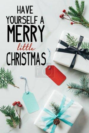 """Foto de Vista superior de regalos de Navidad con ramas de abeto y las etiquetas en la mesa de mármol con inspiración """"tiene usted mismo un feliz pequeño Navidad"""" - Imagen libre de derechos"""