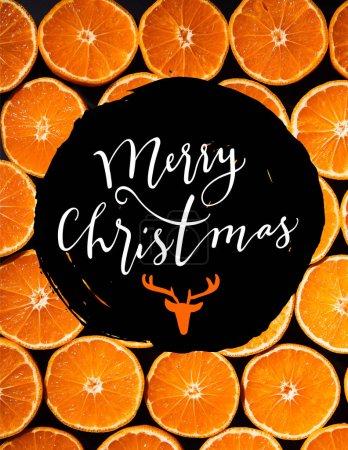 Photo pour Plein cadre des moitiés de mandarines coupées disposées sur un fond noir avec l'inscription «joyeux Noël» avec tête de cerf - image libre de droit