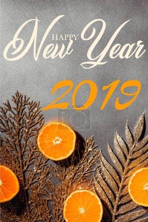 Photo pour Lay plat avec mandarines fraîches et décoratifs brindilles d'or sur fond gris avec l'inscription «happy new year 2019» - image libre de droit