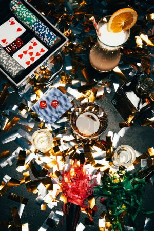 Photo for Elevated view of alcoholic cocktails, playing cards, poker chips and party horns on table covered by golden confetti - Royalty Free Image