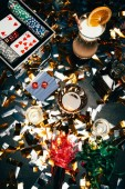 elevated view of alcoholic cocktails, playing cards, poker chips and party horns on table covered by golden confetti