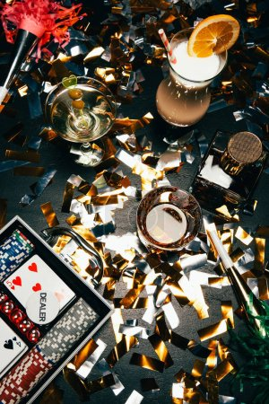 top view of alcoholic cocktails, playing cards, poker chips and party horns on table covered by golden confetti