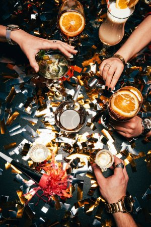 cropped image of friends with luxury watches celebrating alcohol at table covered by golden confetti