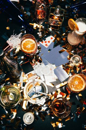 Photo for Flat lay with cigarettes, alcoholic cocktails, whiskey and party horns on table covered by golden confetti - Royalty Free Image