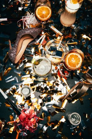 Photo for Elevated view of female shoes on high heel, ashtray with cigarettes, alcoholic cocktails and party horns on table covered by golden confetti - Royalty Free Image