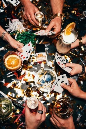 cropped image of friends with alcoholic cocktails playing poker at table covered by golden confetti