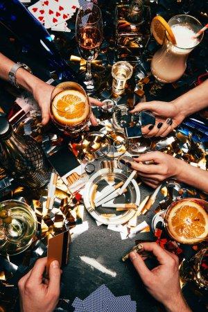 Foto de Imagen recortada de hombre con tarjeta de crédito y billete enrollado va a oler cocaína mientras sus amigas a celebrar con alcohol y cigarrillos en la mesa cubierta de confeti dorado - Imagen libre de derechos