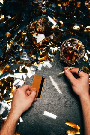 partial view of man with rolled banknote and credit card going to sniff cocaine at table covered by golden confetti