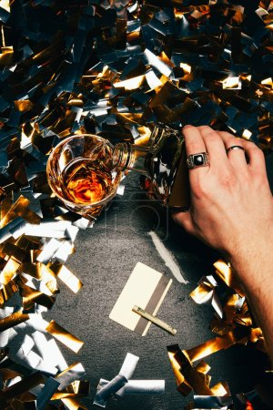 cropped image of man pouring whiskey into glass near cocaine with rolled banknote and credit card on table covered by golden confetti