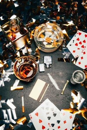 Photo pour Vue d'en haut des cartes à jouer, cigarettes, whisky, roulé de billets de banque, carte de crédit et de la cocaïne sur table recouverte de confettis or - image libre de droit