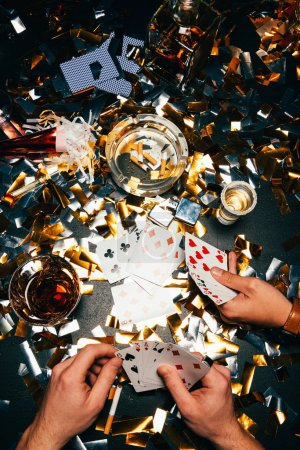 cropped image of male friends and playing poker with alcohol and cigarettes at table covered by golden confetti