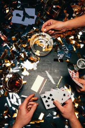 Photo pour Vue partielle des hommes jouant au poker avec la cocaïne, l'alcool et des cigarettes sur la table recouverte de confettis or - image libre de droit