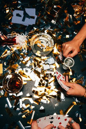 cropped image of male friends playing poker at table covered by golden confetti