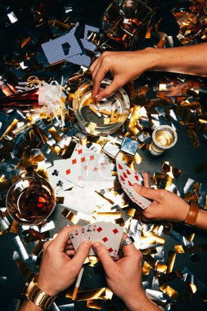 partial view of men smoking cigarettes and playing poker at table covered by golden confetti
