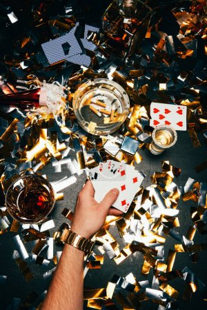 cropped image of man with playing cards and alcohol sitting at table covered by golden confetti