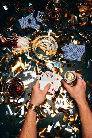 partial view of man with playing cards and alcohol sitting at table covered by golden confetti