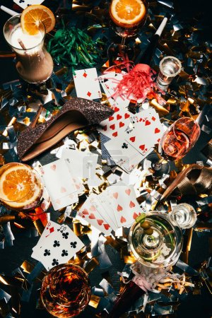 Photo for Top view of female shoes on high heels, playing cards, alcoholic cocktails and party horns on table covered by golden confetti - Royalty Free Image