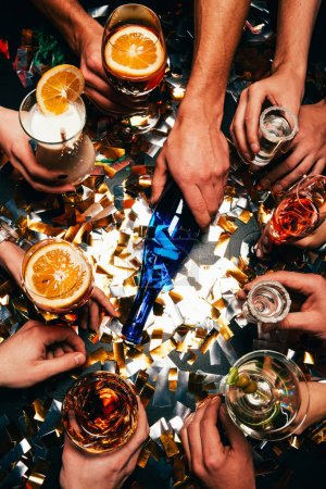 partial view of friends with various alcoholic cocktails playing spin the bottle at table covered by golden confetti