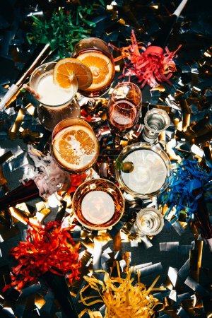 top view of various alcoholic cocktails and party horns on table covered by golden confetti