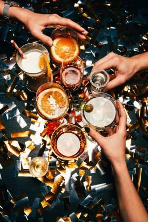partial view of friends clinking by cocktail glasses at table covered by golden confetti