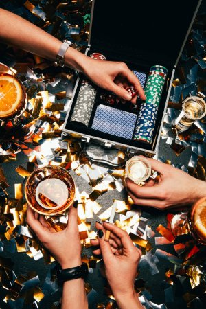 Photo for Partial view of friends celebrating with alcohol, cigarettes and playing cards at table covered by golden confetti - Royalty Free Image