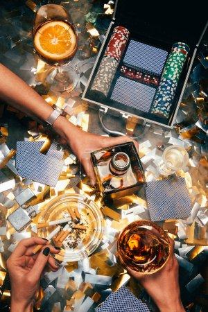 Photo pour Image recadrée de femmes célébrant avec l'alcool, de cigarettes et de poker jetons avec des cartes à jouer sur une table recouverte de confettis or - image libre de droit